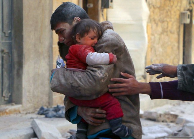 A boy rescues his sister from underneath the rubble of their home in Syria