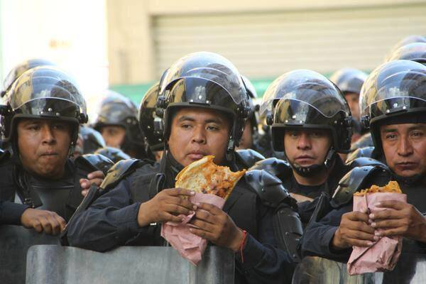 Mexican police having quesadillas for lunch break during protests