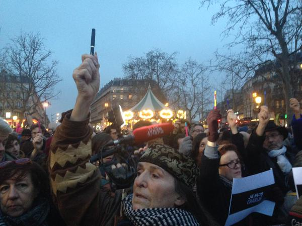 People holding pens in the air at a gathering in Paris to show support after terrorist attack