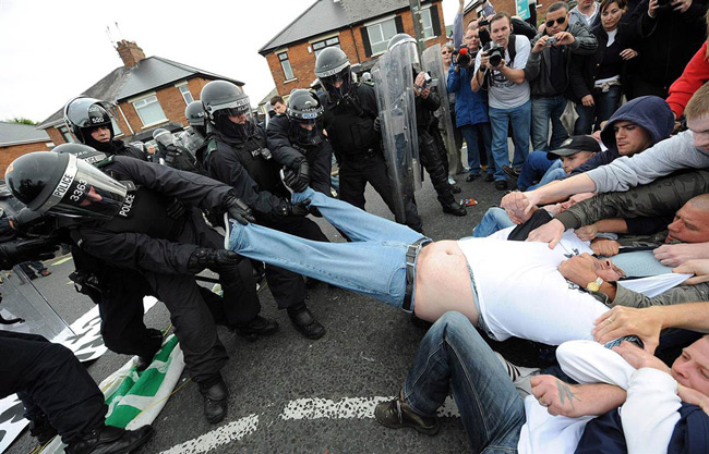 Police and rioters come together to help fat man out of trousers.