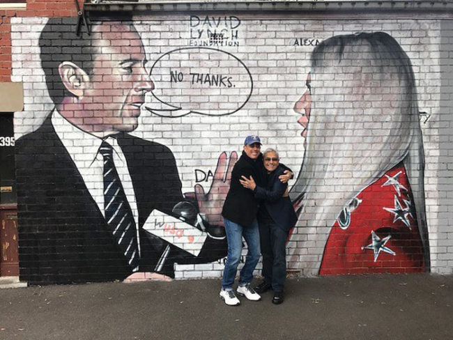 Jerry Seinfeld in front of a mural of himself rejecting Kesha's hug