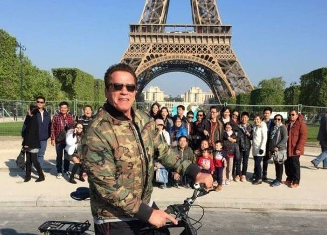 Tourists trying to take a picture at the Eiffel Tower get photobombed by a cyclist