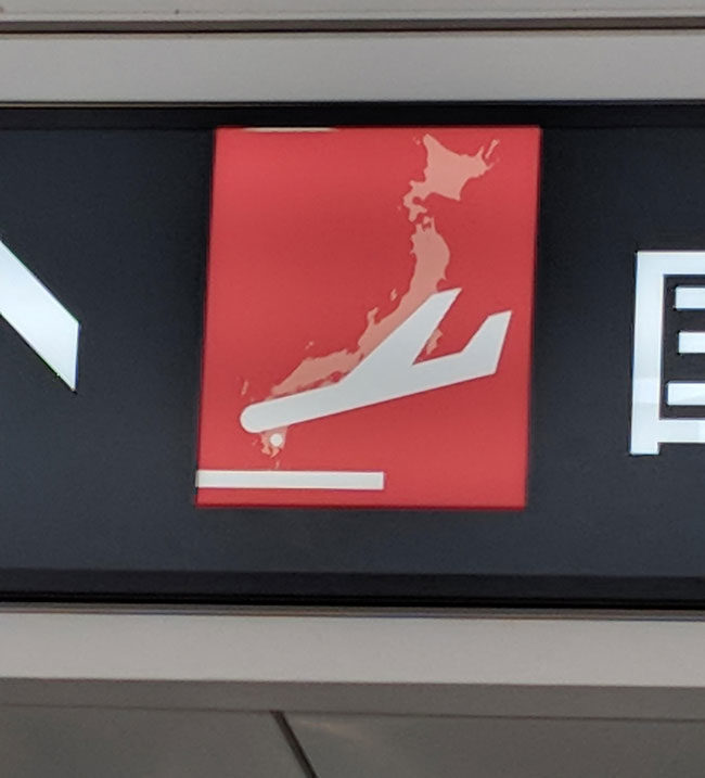 The outline of Japan on the sign makes it look like the plane is crashing in a ball of flames