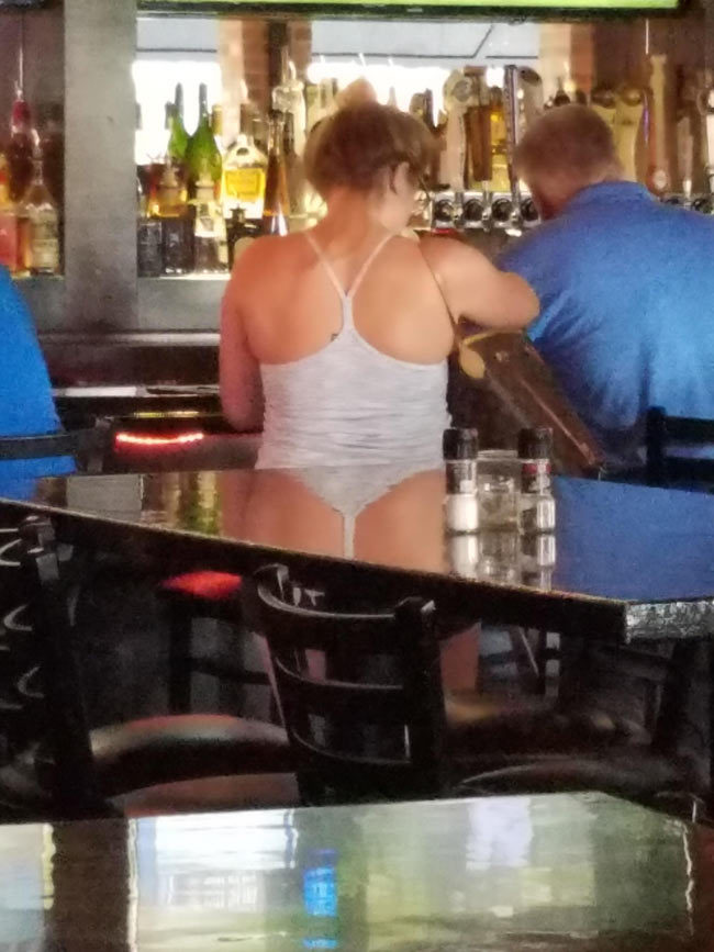 The reflection of her tank top on the table